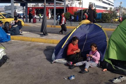 A woman and girl outside a tent at Piraeus port