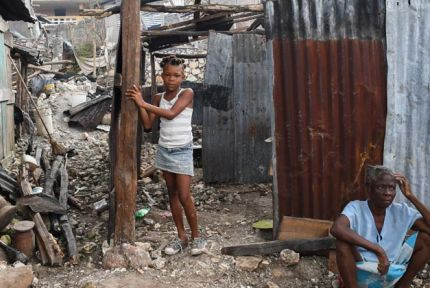 Girl and woman outside storm-damaged house