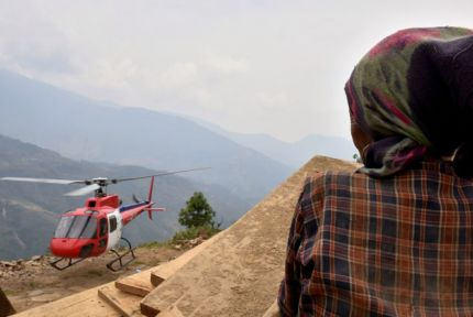 A helicopter carrying food supplies from CARE arrives in Bolgaon village