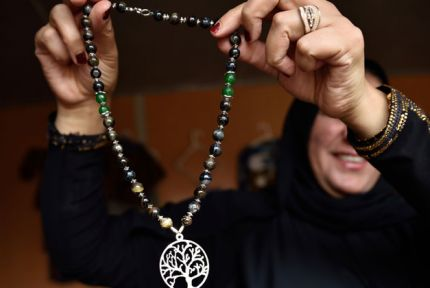 A woman holds a necklace