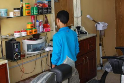 A refugee boy working in a barbershop in Jordan