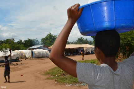 Woman carrying plastic bowl in tent camp, Malawi