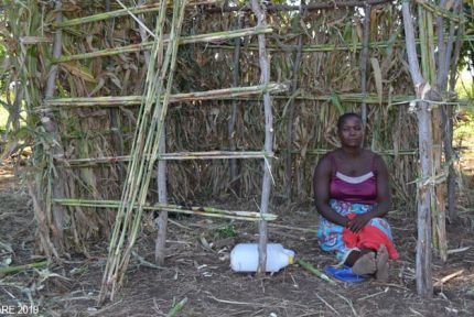 Rhoda Benford in front of temporary shelter in Malawi