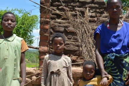 Aida and her children in front of her damaged house