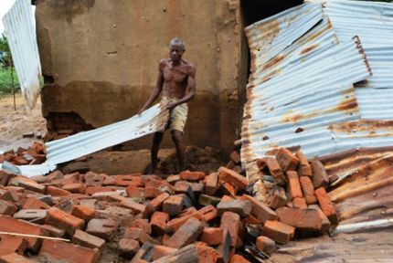 A man moves rubble outside his flood-damaged house in Malawi