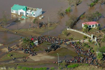 Aerial shot of stranded people surrounding helicopter, Mozambique