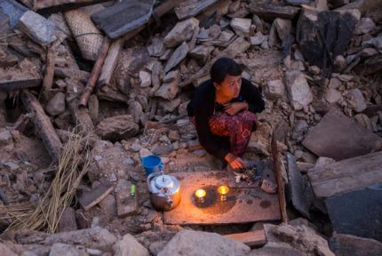 19-year-old Pasang sits on the rubble of her ruined house