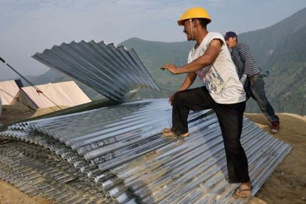 Men unload corrugated roofing sheets in Nepal