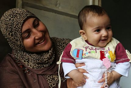 Syrian refugee woman holding a baby
