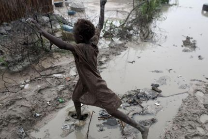 A girl leaps over a puddle at Bentiu camp, South Sudan