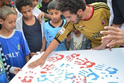 Youth and women in Sanaa create art for their neighborhood that promotes messages of peace as part of CARE's Foundation for Peace project.