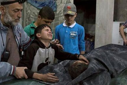 A young boy cries over a dead body in Syria