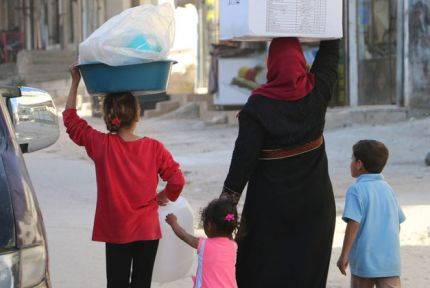Woman and children carrying hygiene kit in Syria