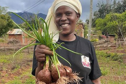 A farmer in Tanzania with her onion crop