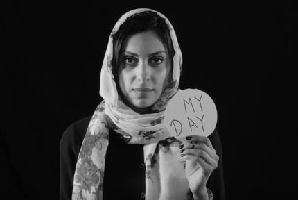 Yousra, a Yemeni woman, holding a sign