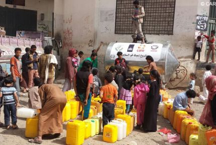 People in Sanaa line up to collect water at water tank donated by CARE