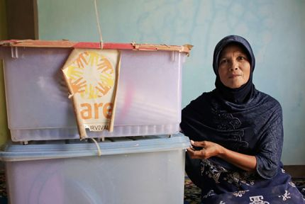 Ernawati pictured with the original CARE packages that she received in the immediate aftermath of the tsunami © CARE / Josh Estey