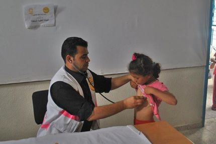Dr Ghassan Qaraman examines a girl at a mobile health clinic in Gaza © PMRS