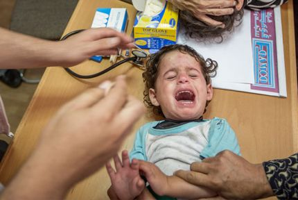 A young girl is treated by staff from the Palestinian Medical Relief Society © CARE / Alison Baskerville