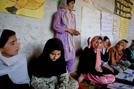 Young girls attend a school that is being held in the front room of a house in Afghanistan