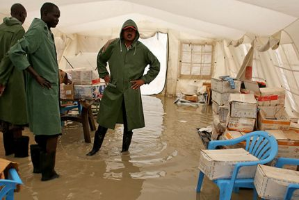 CARE nutrition officer Demelash Habtie centre with colleagues in the flooded CARE nutrition centre at Bentiu camp © CARE / Josh Estey