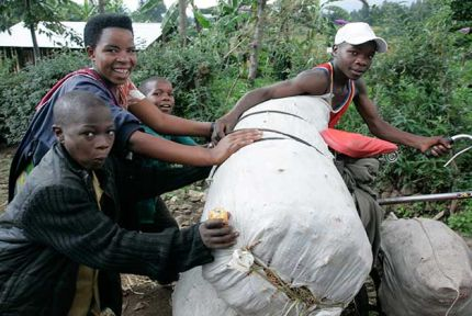 A family pushes their belongings on a bicyle in Rwanda in 2009. © CARE / Peter Caton