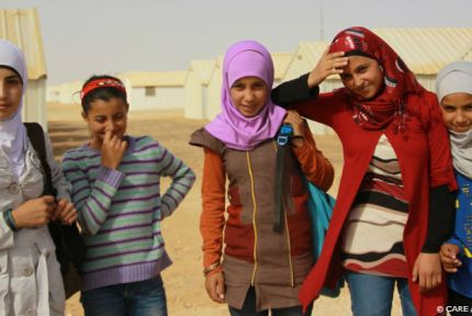 Five young Syrian girls smile at the camera