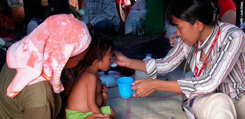 Marlina being fed high energy milk to treat malnutrition in the aftermath of the tsunami © CARE