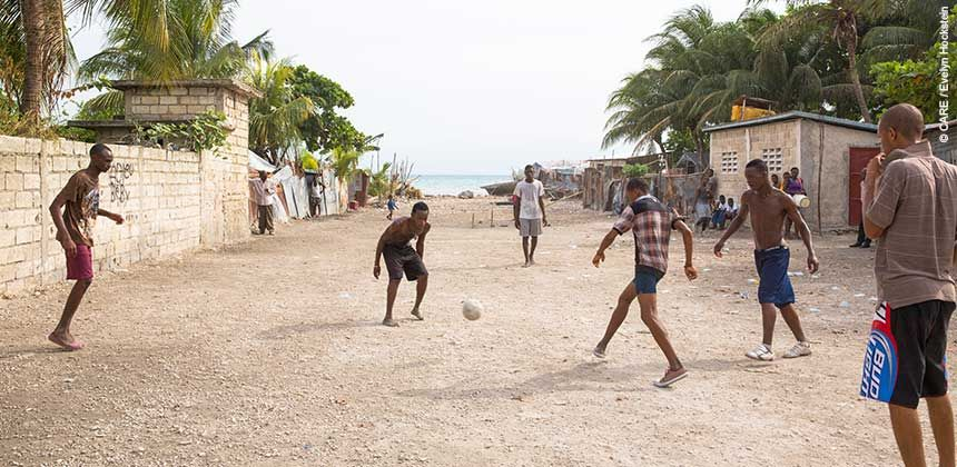 Boys play football in an open area which formerly housed displaced people after the earthquake © CARE / Evelyn Hockstein
