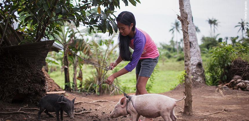Jinky with the piglets she bought with a cash grant from CARE © CARE / Mario Ignacio