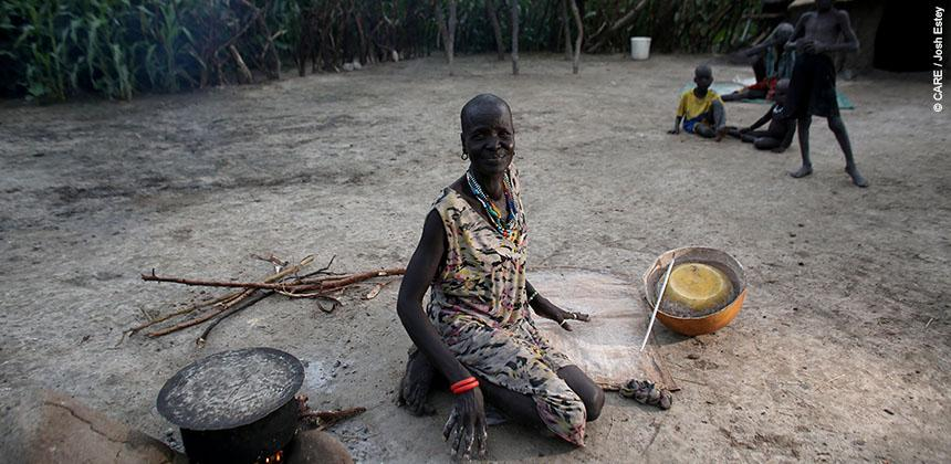 "A mother prepares boiled sorghum for her family. She said: ""This will be the only meal we'll eat today."" © CARE / Josh Estey"