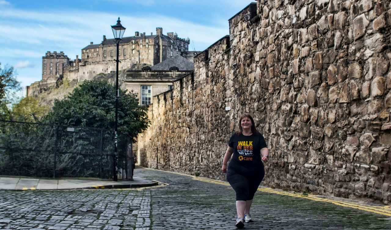 A woman in a Walk In Her Shoes T shirt walks through a Scottish street.