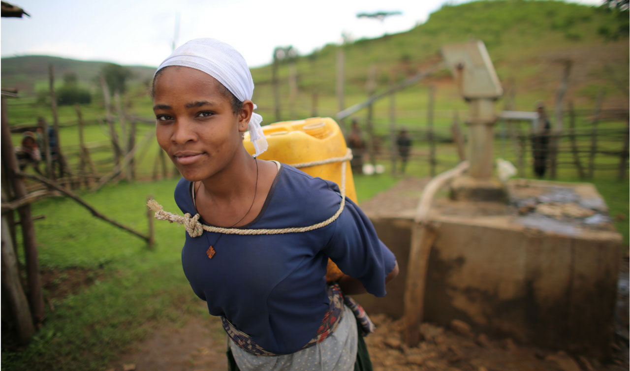 A woman walks through a village with a water can on her back